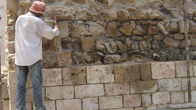 A mason restores the cut stone exterior of a 2nd-century defensive tower at the ancient city of Tyre in Lebanon.