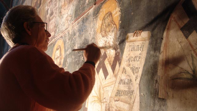 A paintings conservator carefully restores the damaged frescoes in the Peribleptos church in Ohrid, Macedonia.