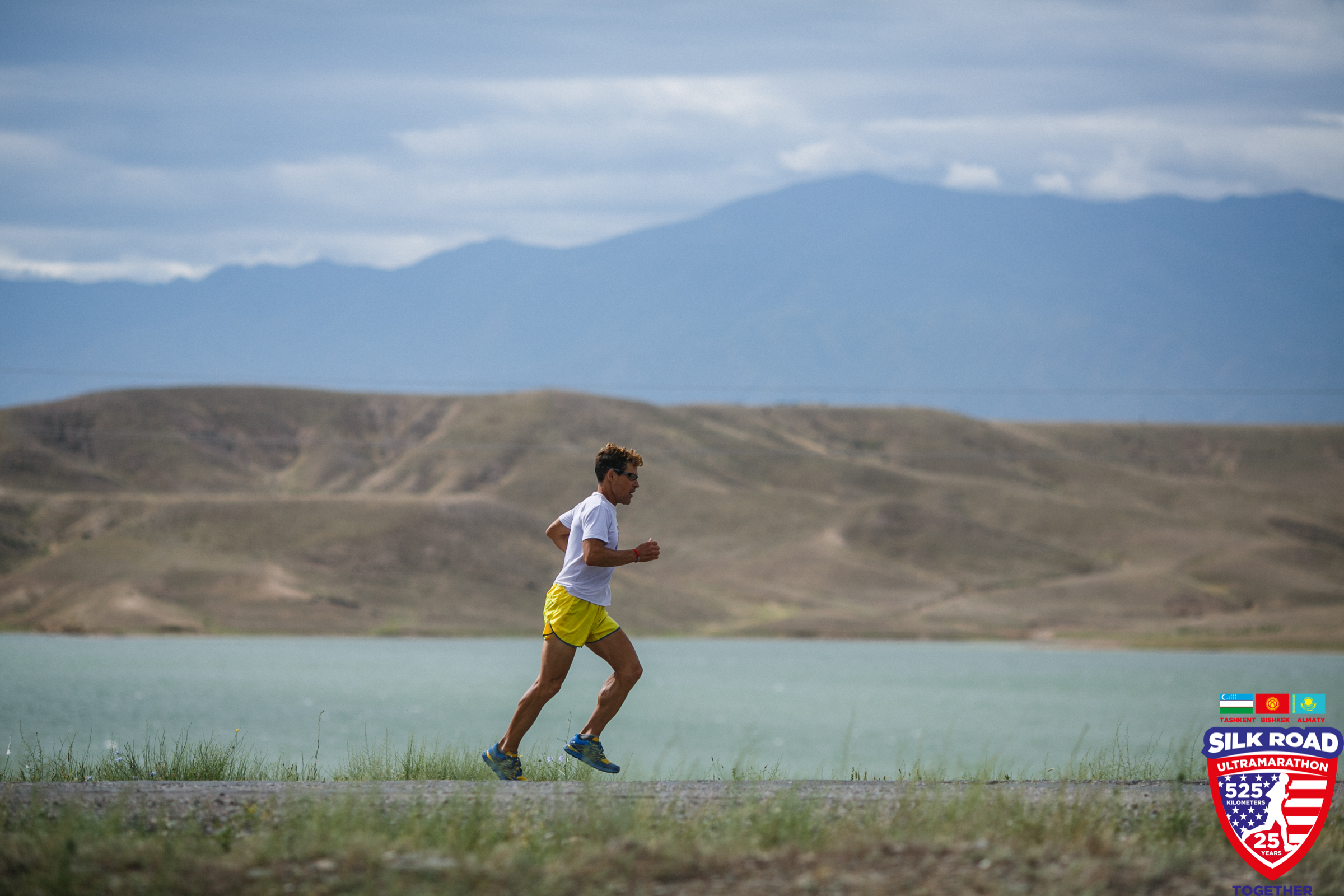 Dean running on road with mountains in the background