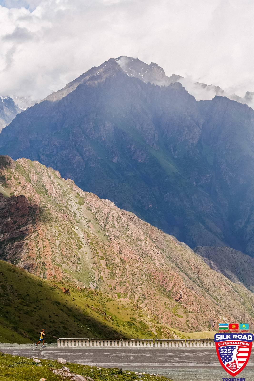 Dean is a tiny figure in a yellow shirt next to the towering mountains of the Kyrgyz Republic