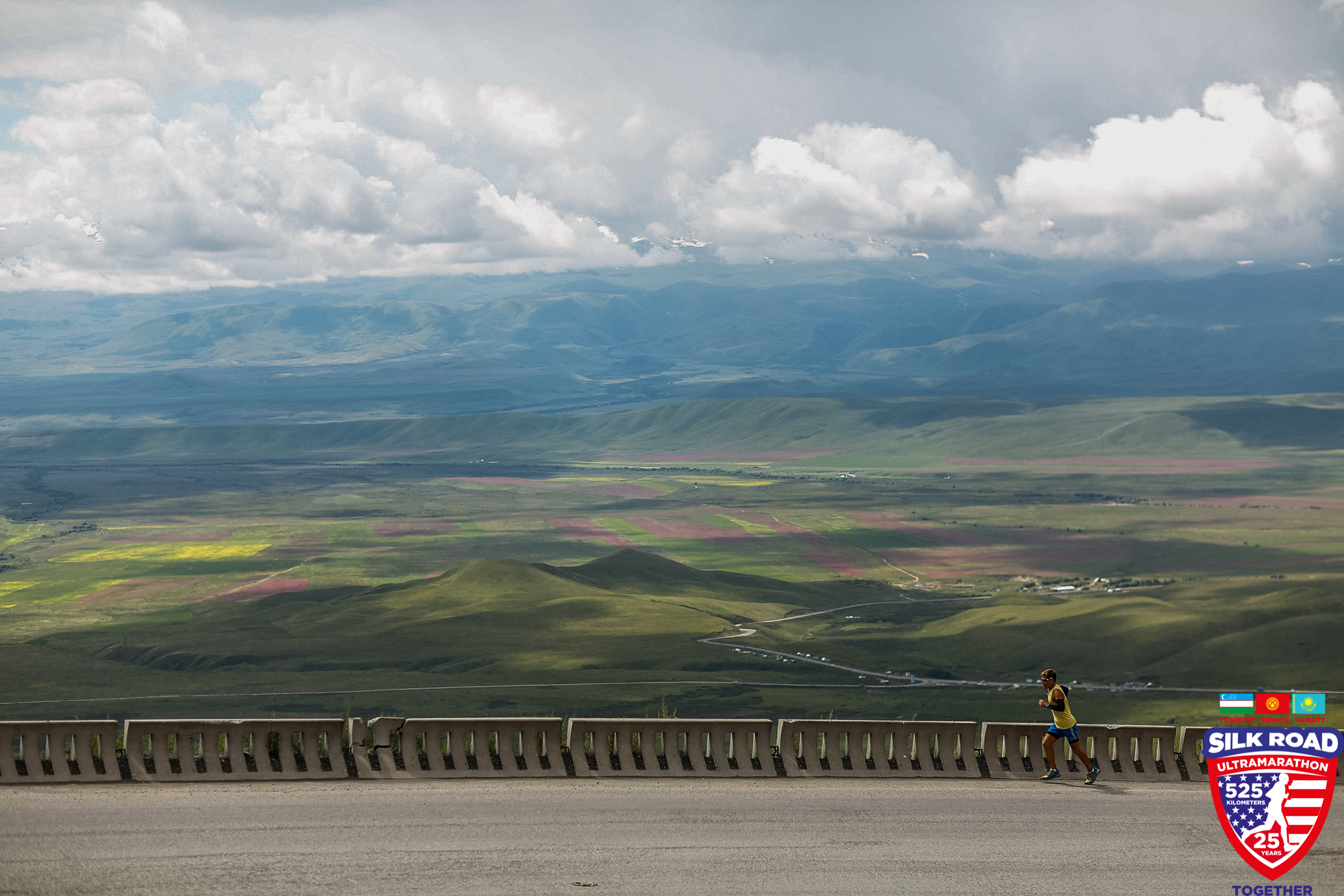 Dean runs next to an expansive view of fields, mountains, and clouds