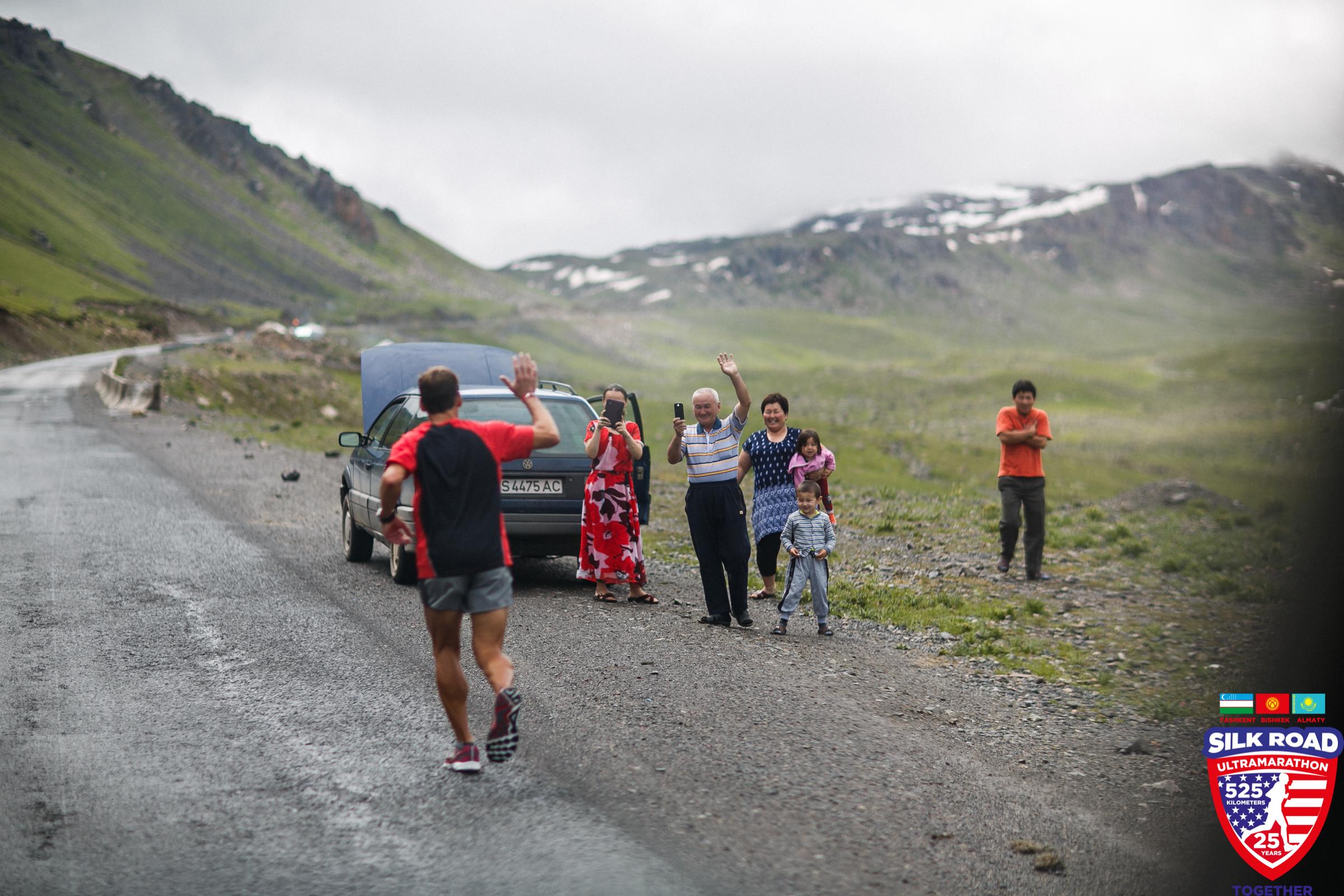 A Kyrgyz family stops to capture photos of Dean as he runs by