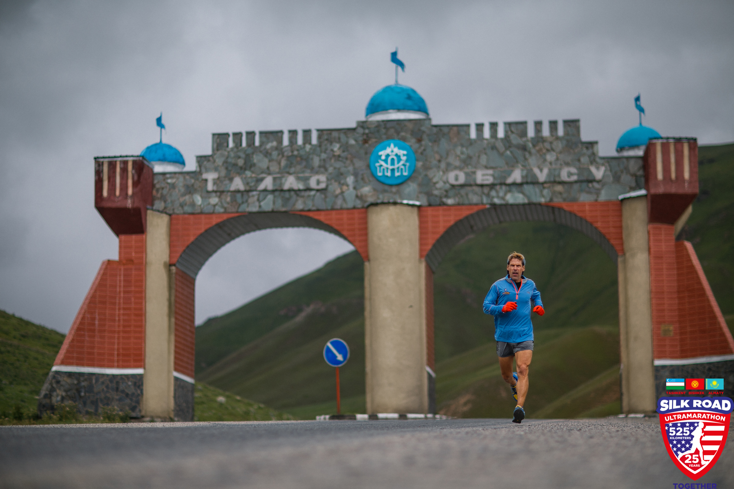 Dean running through a large archway in the Kyrgyz Republic