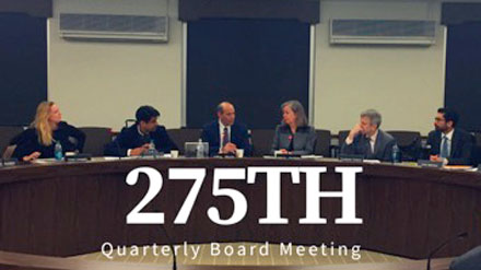 """Six adults sitting behind a long round desk with the title """"275th Quarterly Board Meeting"""" layered on top"""