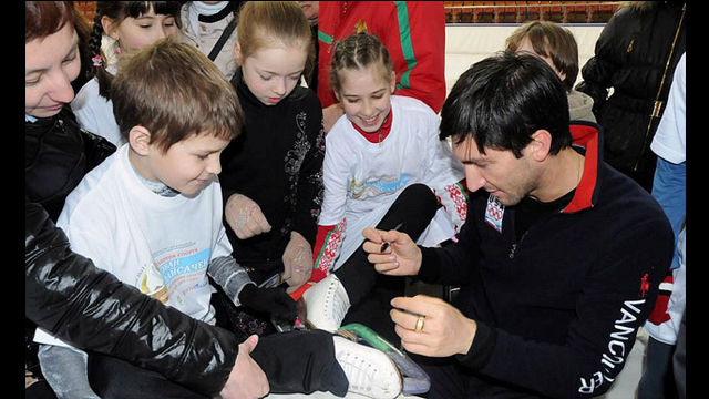 Evan Lysacek signs ice skates for young fans.