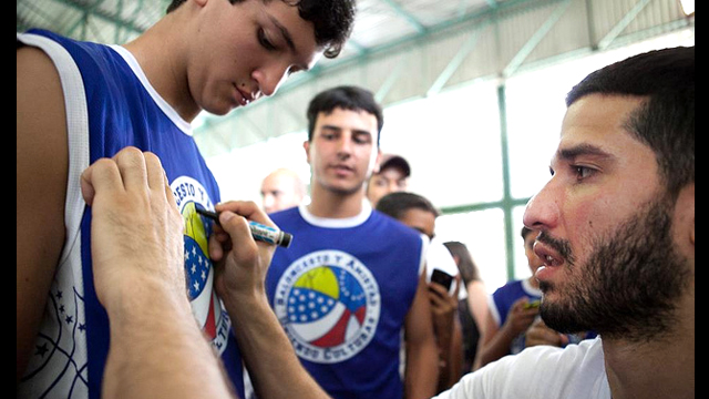 Teenage fans line up for Greivis Vasquez's autograph after a basketball session.