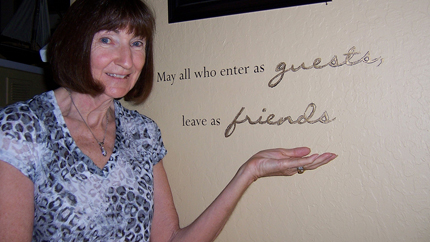 "Photo of Anita Bevan next to plaque saying ""May all who enter as guests leave as friends."""