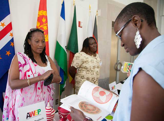 African woman shows product book to potential customer at B2B showcase