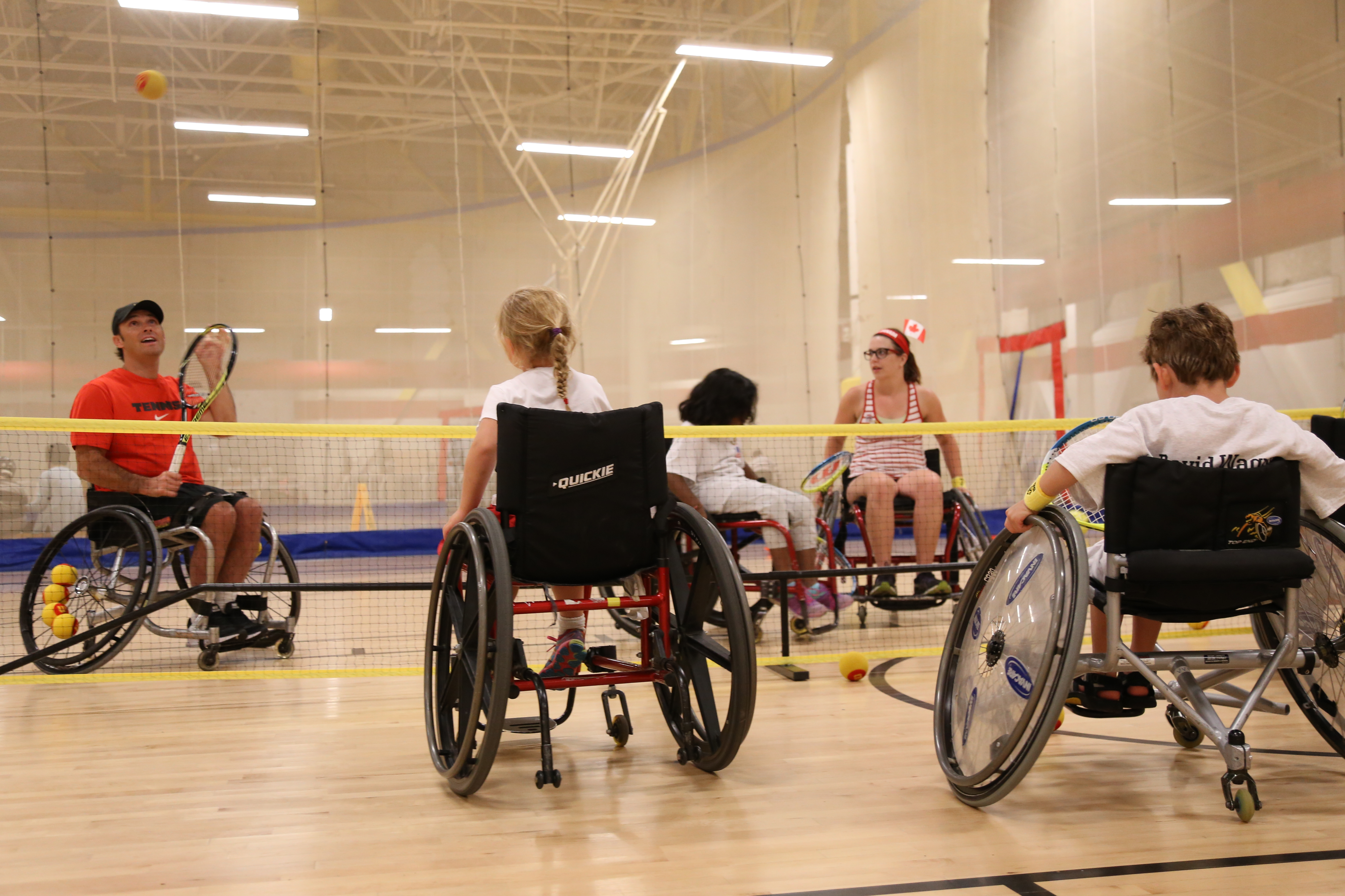 David Wagner and kids in wheelchairs at an indoor tennis court