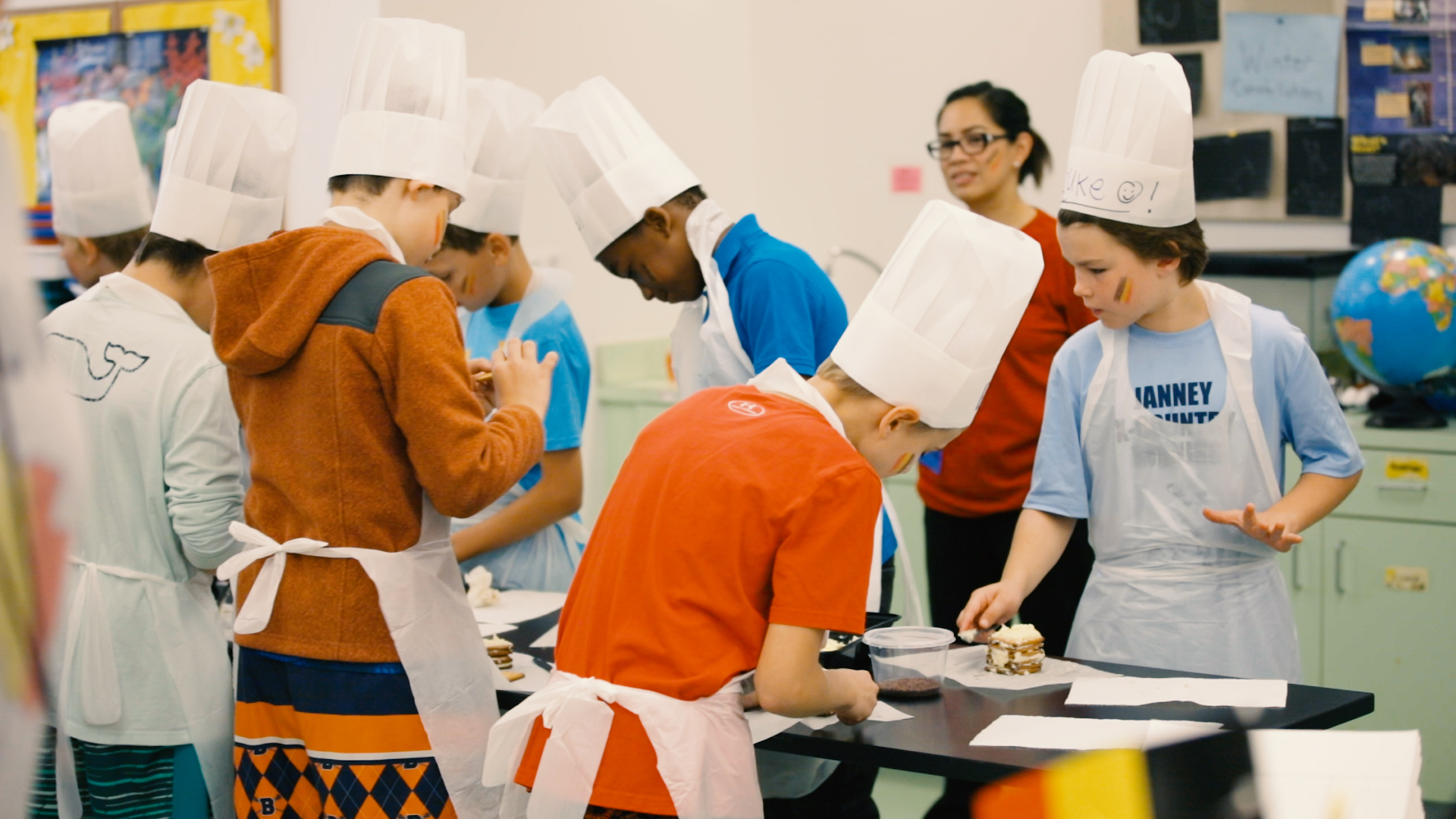 Group of children in a classroom wearing chef hats and aprons
