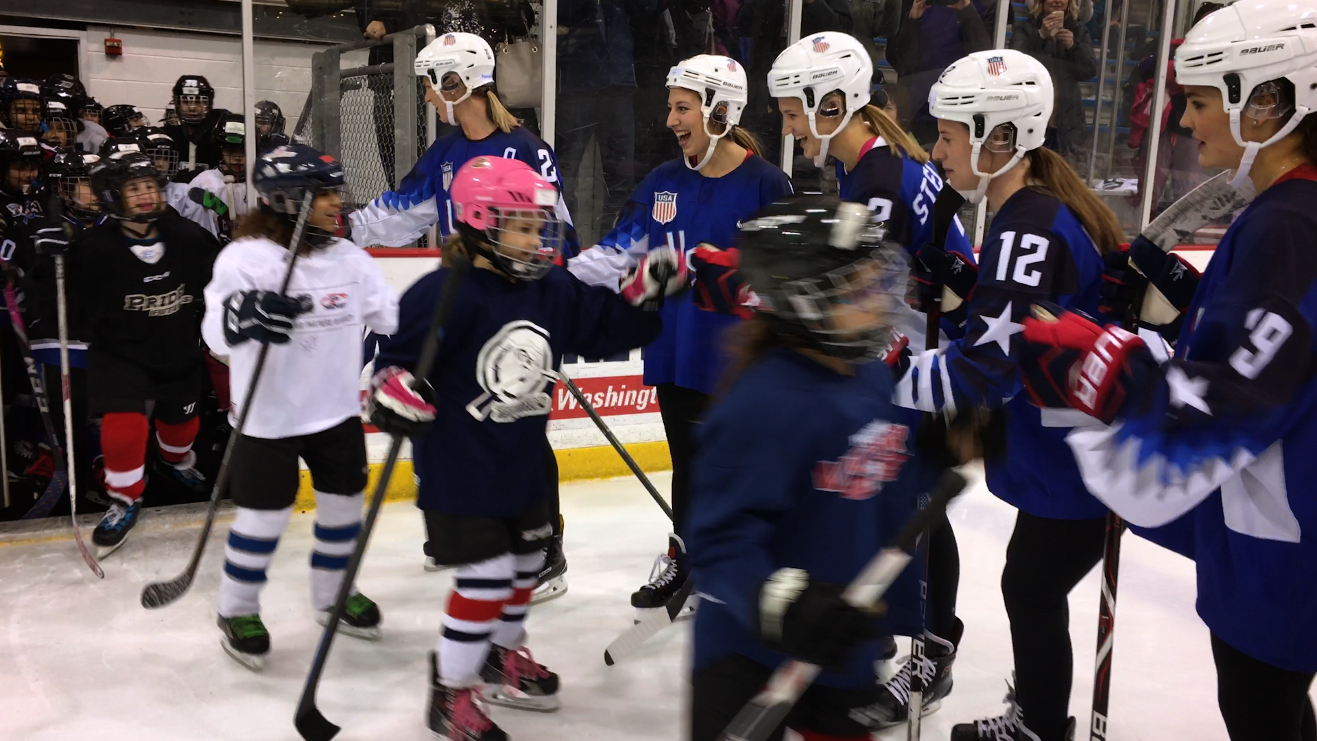 Young women hockey players dressed in gear on an ice rink high five a line of young girls in hockey gear as they enter the rink