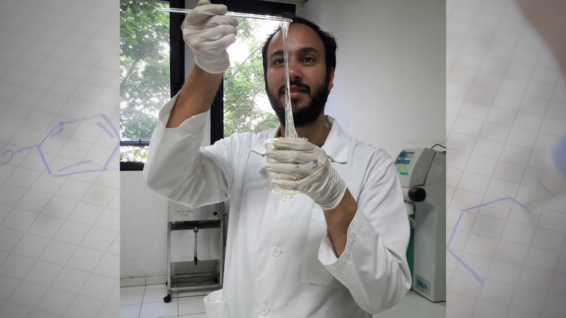Man in lab coat holds sticks above a vile that has long clear sticky substance hanging from the stick into the vile
