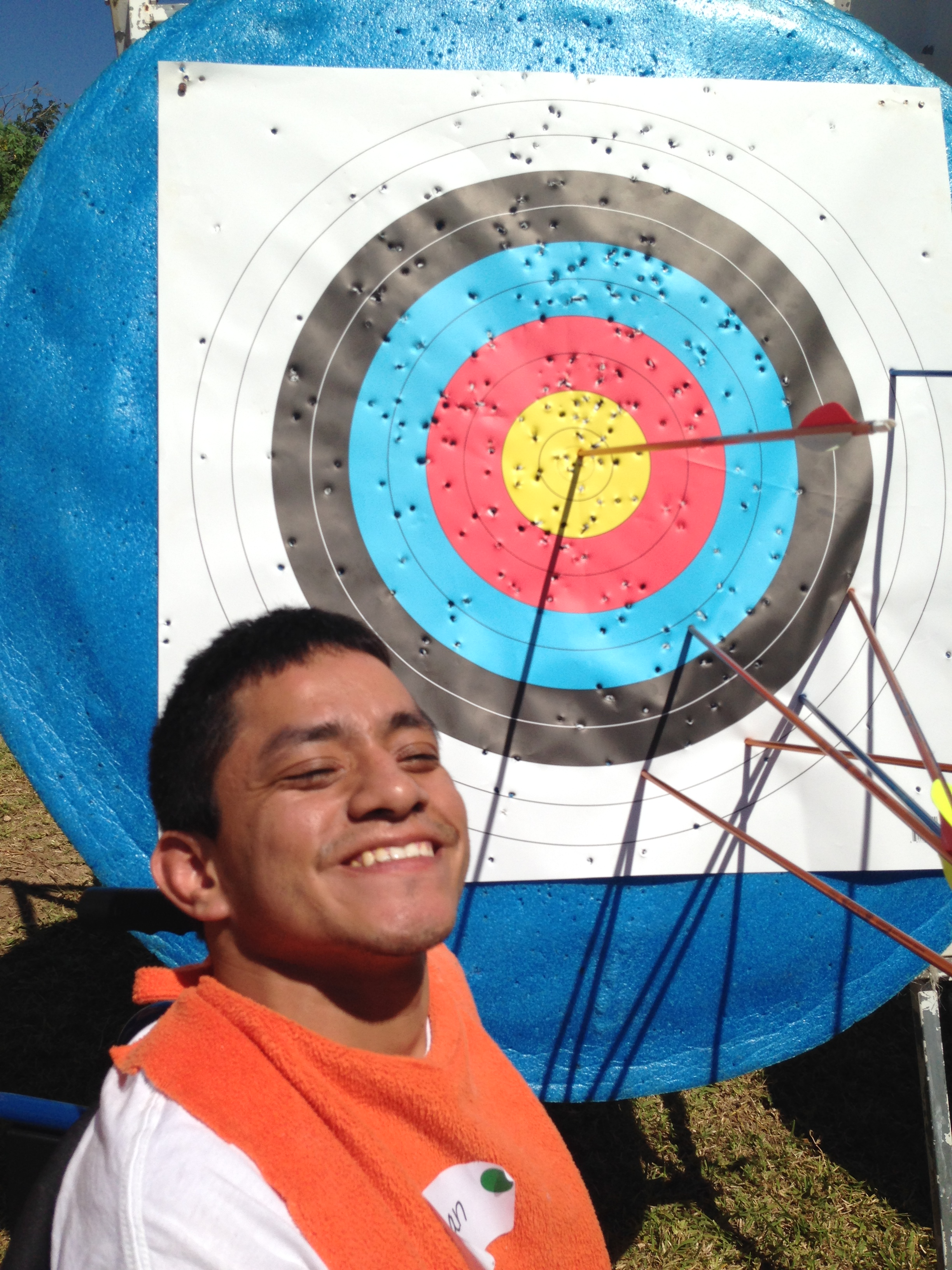 Juan poses by his first-ever bull's-eye during an archery session