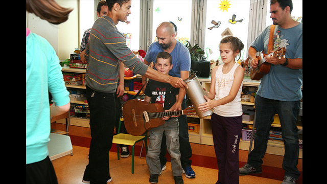 Ozomatli band members help children play along with the band at children's hospital, Centrum Zdrowia Dziecka, in Warsaw, Poland.