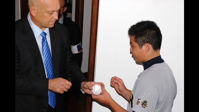 Cal Ripken signs a ball for a young Japanese fan.