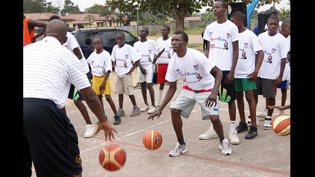 Former NBA Player Bo Outlaw dribbles with a teenager from Congo Brazzaville.