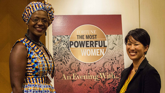 "A woman in African dress and Asian woman standing in front of a sign reading ""Fortune:The Most Powerful Women""."