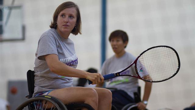 Woman in a wheelchair holding a tennis racquet