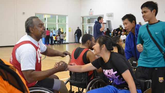 After playing a spirited round of wheelchair basketball, an Indonesian visitor is commended by her opponent.