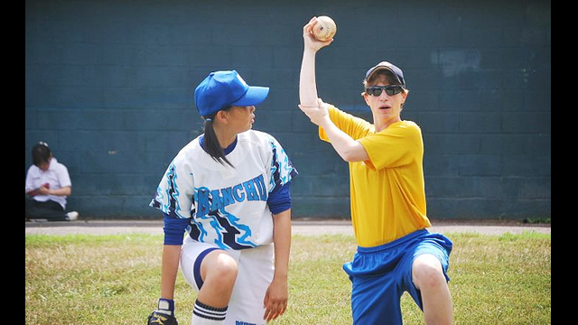 One of the softball players receives some tips on how to maximize her throwing power.