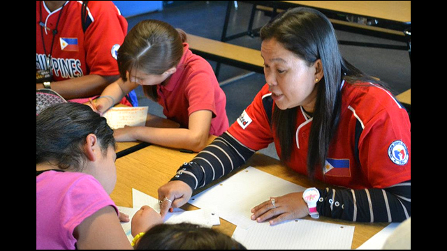A Filipina coach helps a student during class at a local Phoenix-area school.