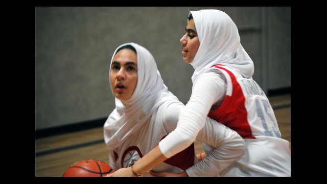 Girls use their new skills during a game of one-on-one.