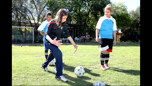 Former U.S. Women's National Team coach Lauren Gregg teaches proper dribbling techniques to young women in Argentina.