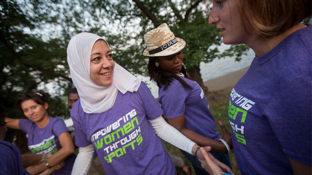 Girl in white headscarf wearing purple tee shirt shaking hands with another girl in a matching shirt
