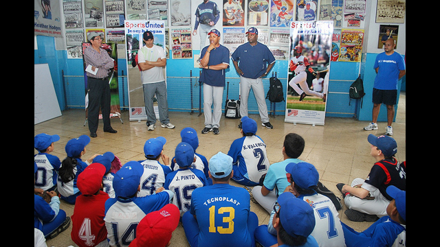 Barry Larkin and Joe Logan speak with young athletes before a baseball clinic in Ecuador.