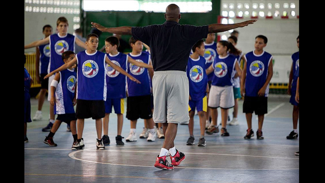Chris Clunie, Senior Coordinator for the NBA's International Basketball Operations, leads warm-up with the young Venezuelans.