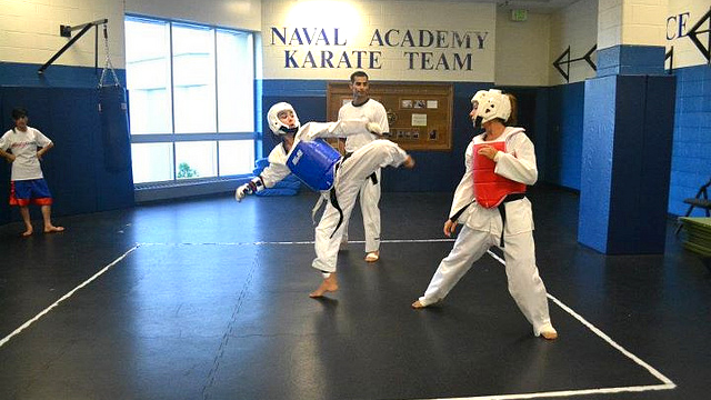 The coaches spar with the Naval Academy's taekwondo team.