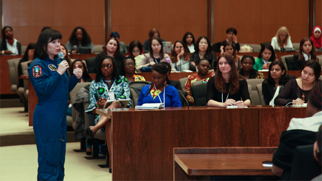 Female NASA astronaut speaking to a group of women in a lecture hall.