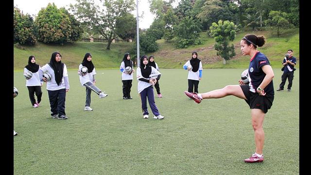 Sports Envoy, Danielle Slaton, gives the girls tips on kicking.
