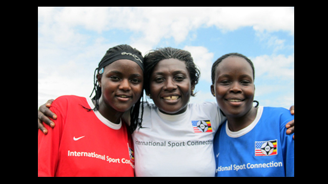 Ugandan soccer coaches dressed in red, white, and blue, pose for a photo in Kampala.