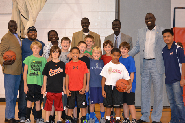 The South Sudanese coaches join a boy's basketball team for practice at a local-area elementary school.