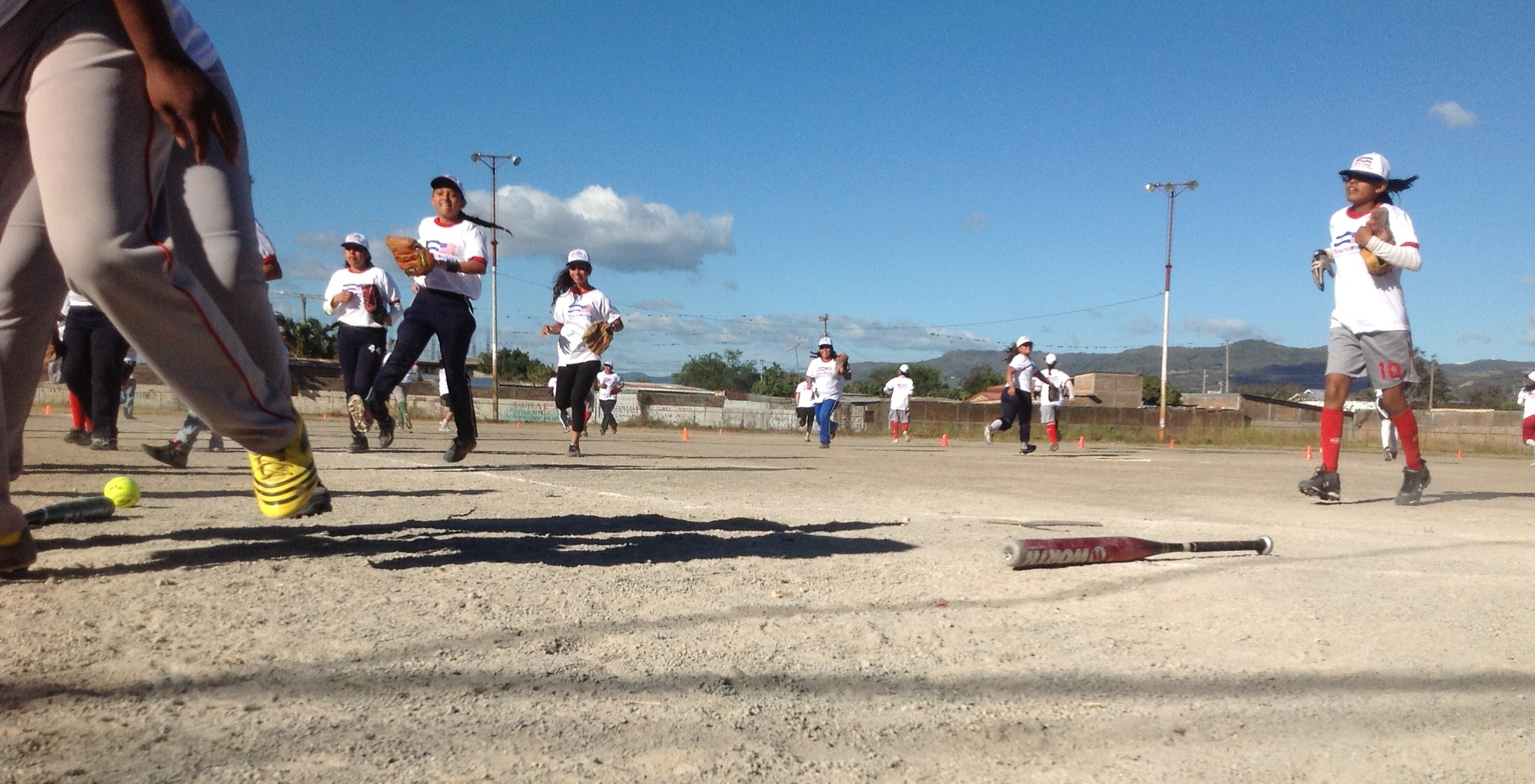 After a fun game of softball with the sports envoys, a team of teenage girls trot off the field.