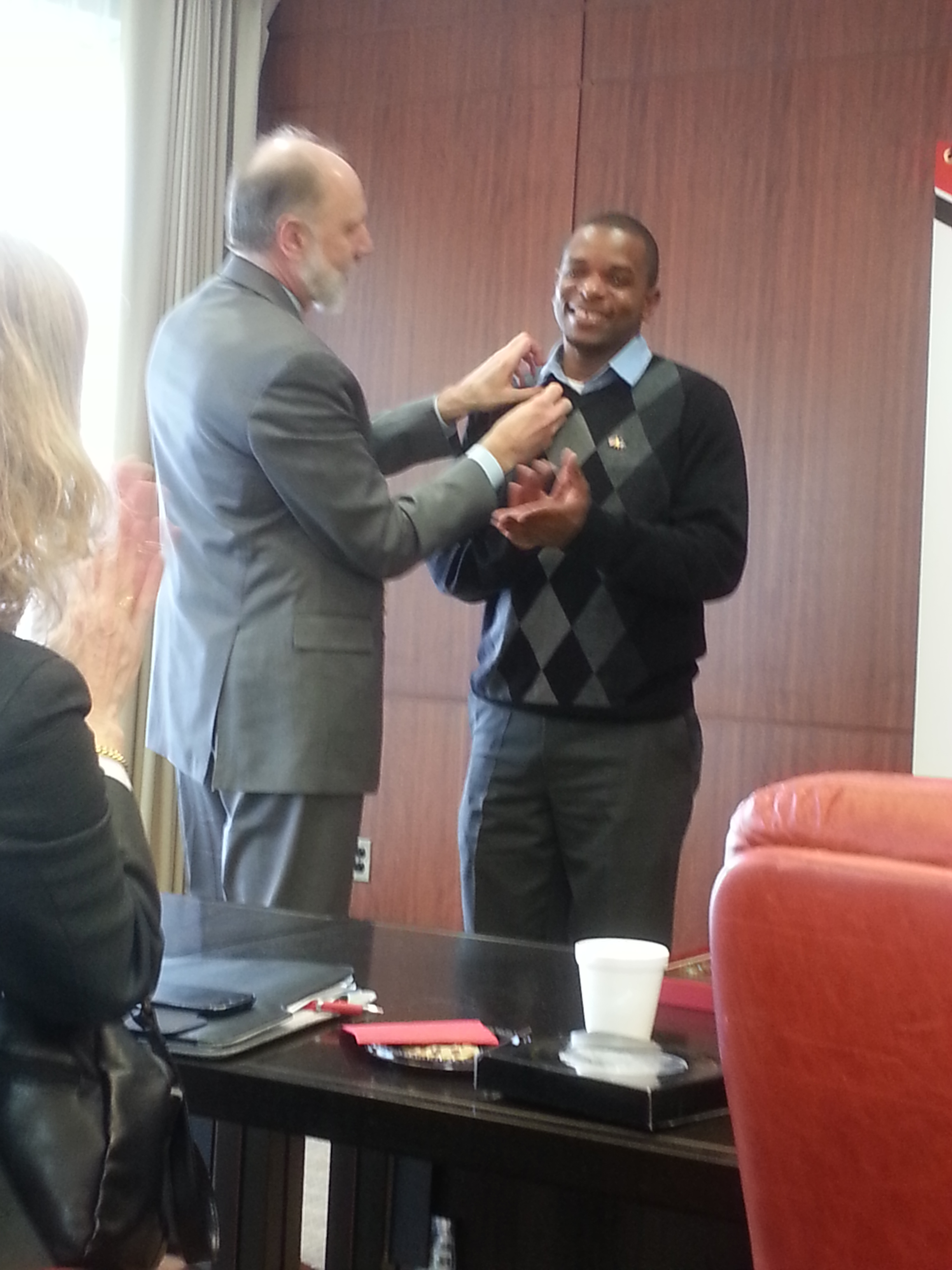 President Baker presenting delegate Bernard with his NIU sport pin