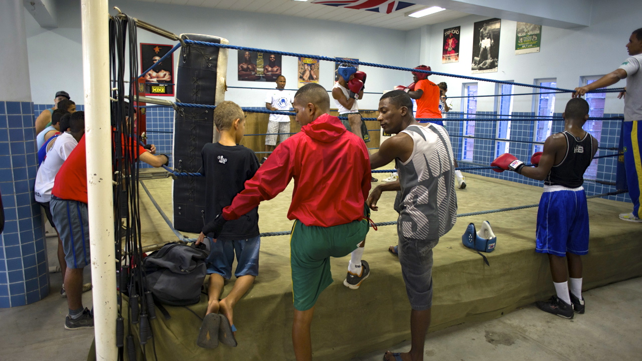 Boxers watching other boxers spar in boxing ring