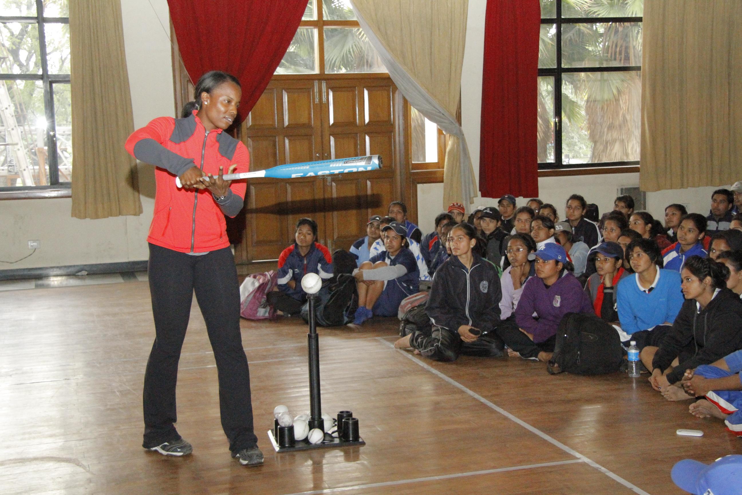 Sports Envoy Natasha Watley provides key tips on batting at a group meeting.