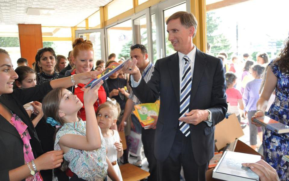 Fulbright English Teaching Assistant Jennifer Birdsall (in red) with U.S. Ambassador to Macedonia Paul Wholers as he hands donated English children's books out to local children at the American Corner Tetovo.