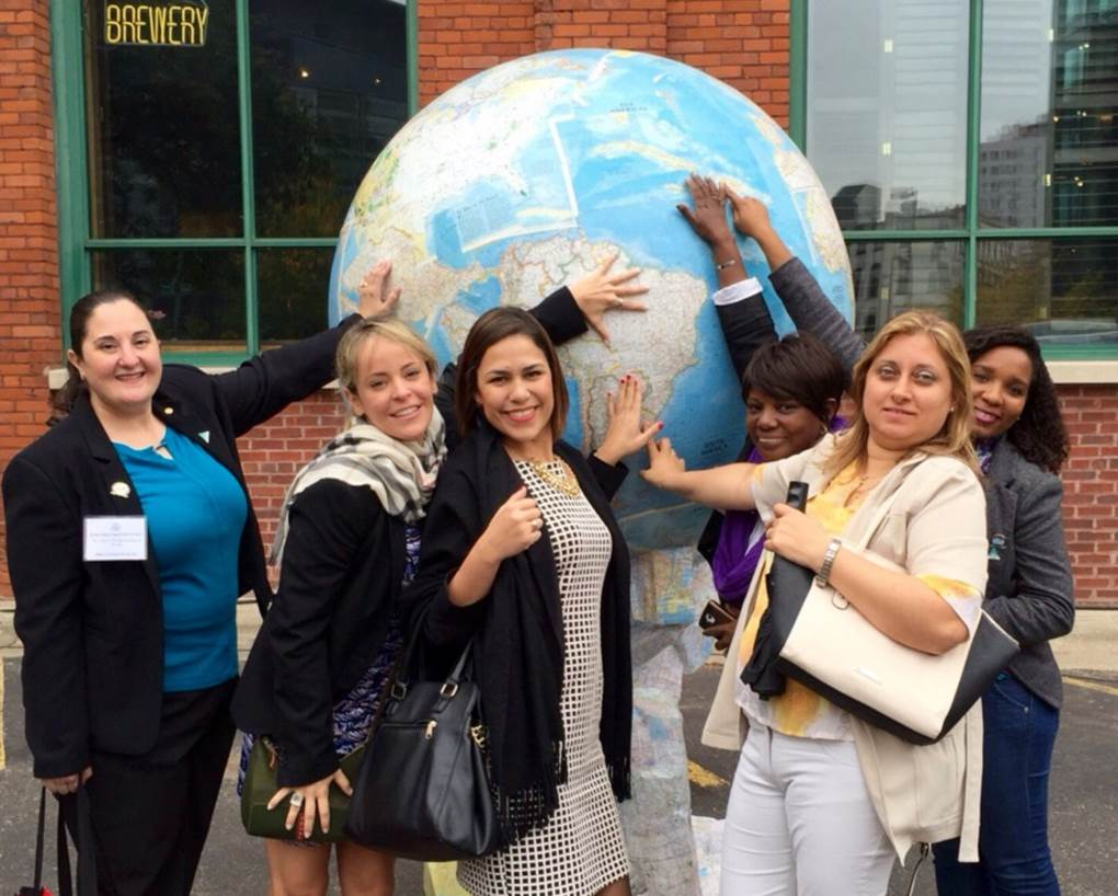 Group of young women touching large globe