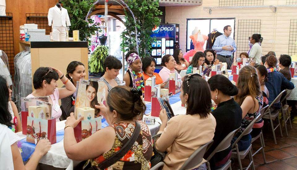 Large group of young women sitting around a table opening gift bags