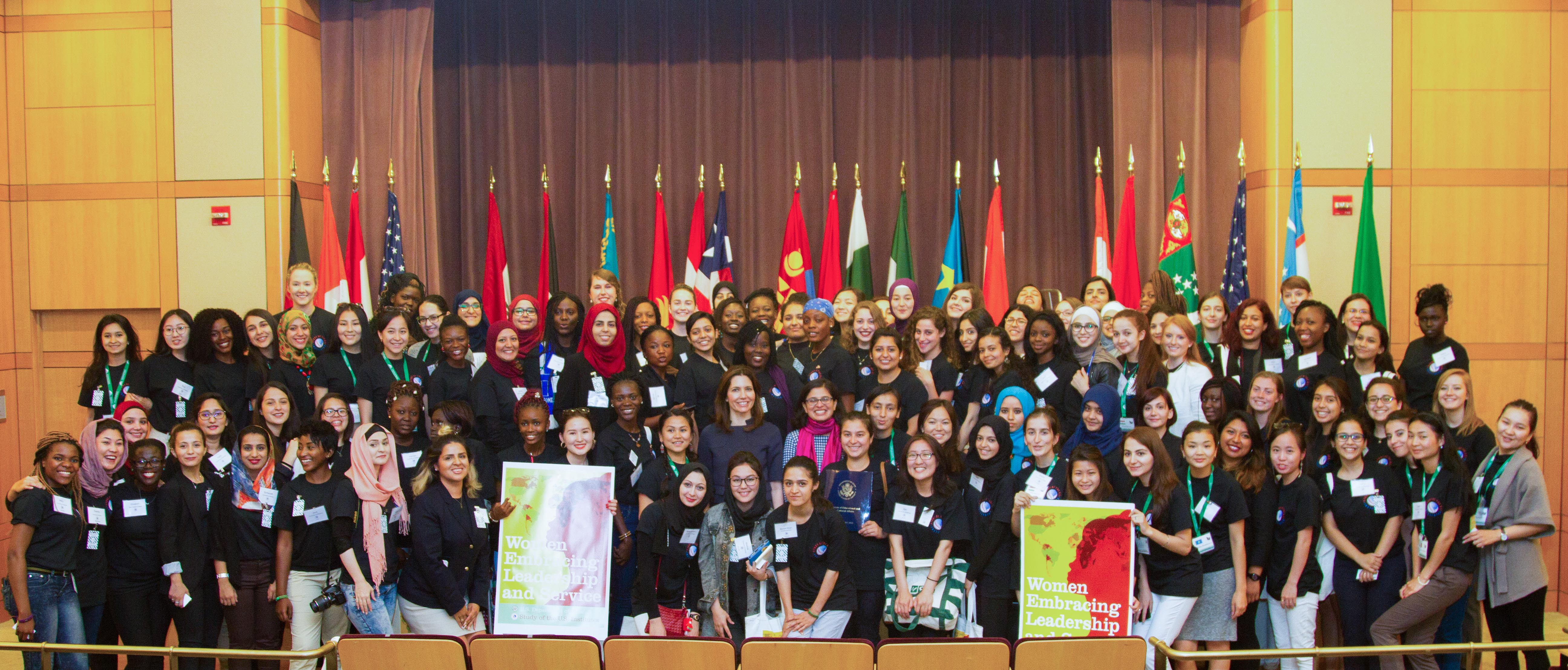 International group of women pose for a group shot in front of flags