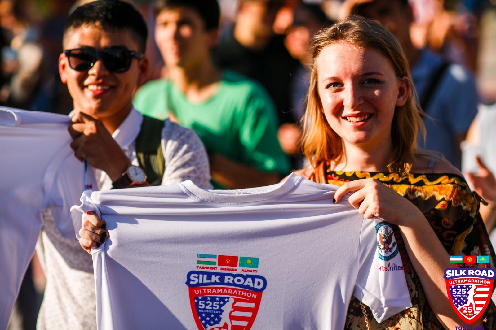 Teens holding up Silk Road Ultramarathon shirt