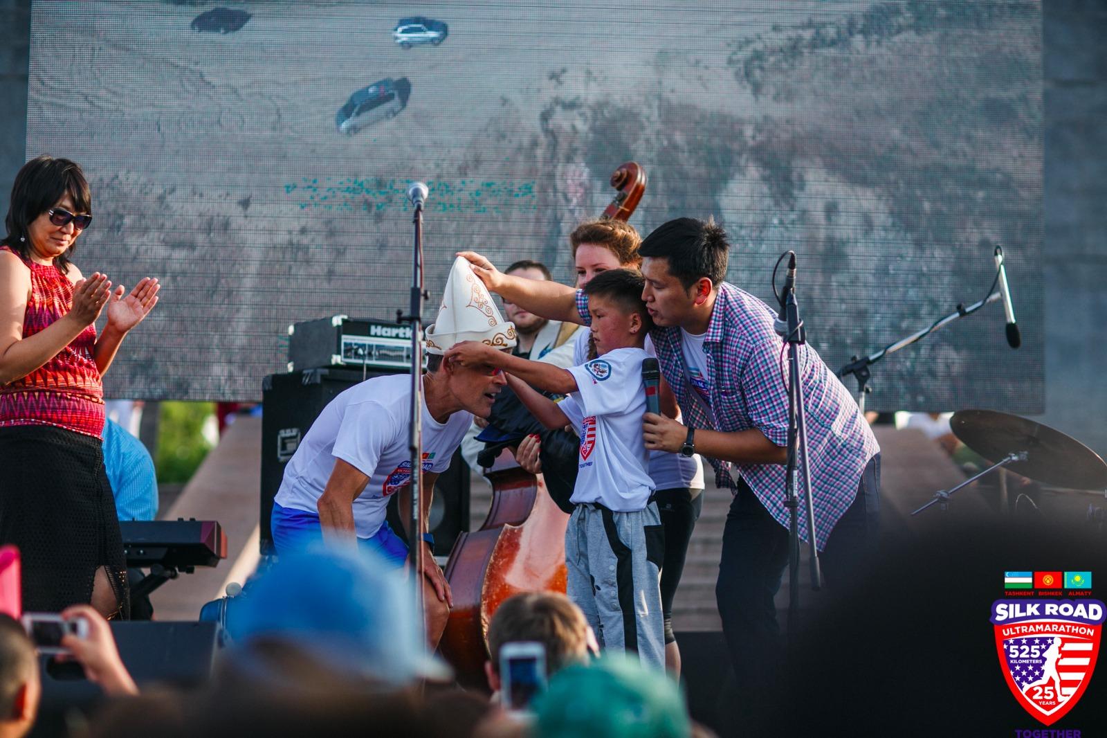 Dean receiving Kyrgyz hat at a concert