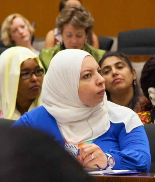 Women with head wrap sitting looking towards speaker at meeting