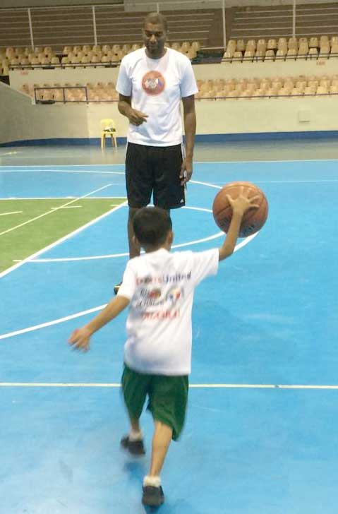 Child dribbling basketball on court towards Derrick Alston