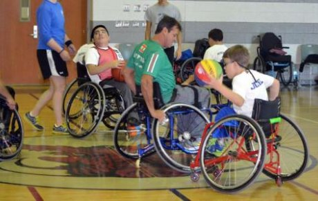 Participants in wheelchairs doing exercise in a gym