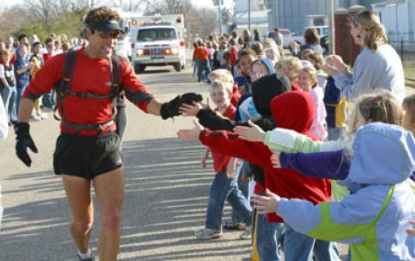 Dean Karnazes giving high five to kids while running