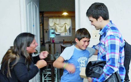 National Youth Science Camp alumnus Gino Tubaro presents an 11 year-old boy with a prosthetic hand he created using a 3D printer.